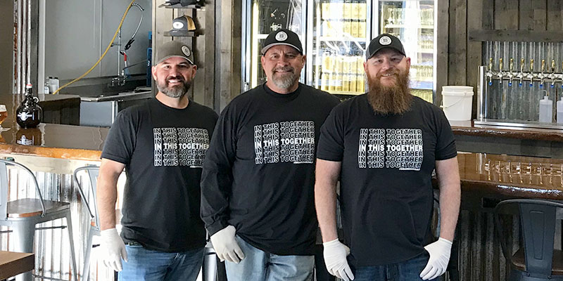 """Joe Novotny, Dan Wood and Josh Malcolm stand together in the taproom at Dying Breed Brewing wearing black t-shirts that say, """"In this together,"""" referring to the COVID-19 pandemic."""