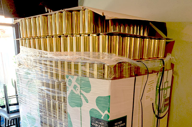 A large pallet of vertically-stacked, brass-colored aluminum cans is shown. The pallet is on the ground and is visibly taller than the person that took the photo.