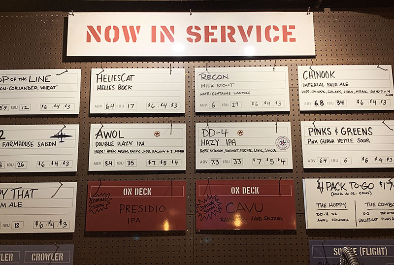 """Available beers are posted on the wall under a """"Now in Service"""" sign. The beers all have military-themed names, such as a helles bock called """"HellesCat"""", an imperial pale ale called """"Chinook"""", and a double hazy IPA called """"AWOL""""."""