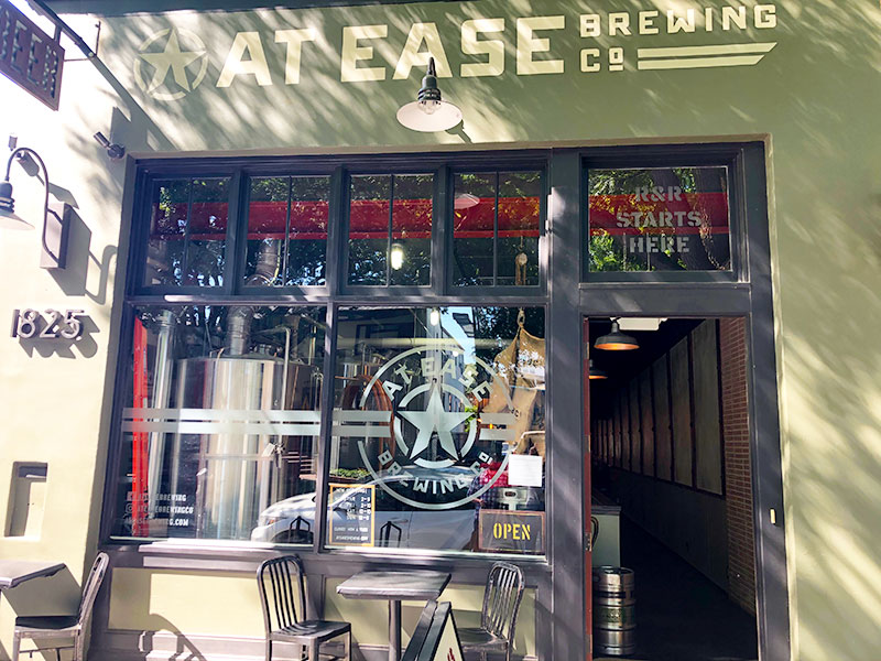 """The olive green exterior of military-themed At Ease Brewing Company is shown. Above the door, stenciled on a window are the words, """"R&R Starts Here."""""""