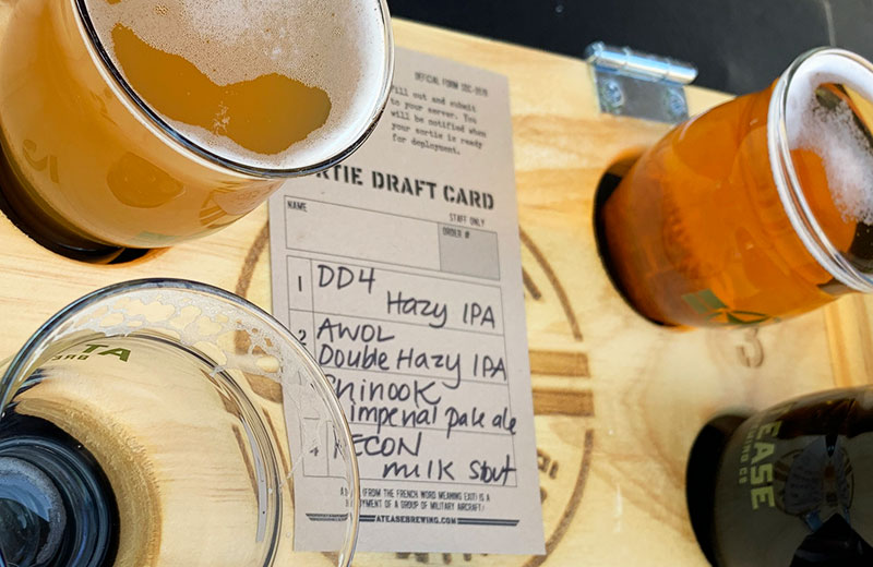 """A military-themed tasting card is shown lying on a flight of beers labeled, """"Sortie Draft Card,"""" and lists the beers to be sampled with names like 'DD4 Hazy IPA', 'AWOL Double Hazy IPA', 'Chinook Imperial Pale Ale', and 'Recon Milk Stout.'"""