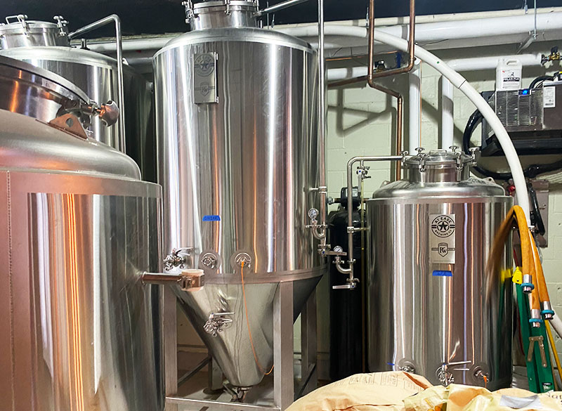 Several large, vertical tanks are seen in the production area at At Ease Brewing in downtown Sacramento.