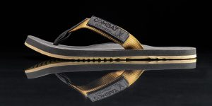 """A sales photo for a Combat Flip Flop brand men's """"coyote"""" colored flip flop called the """"Floperator"""" is shown."""