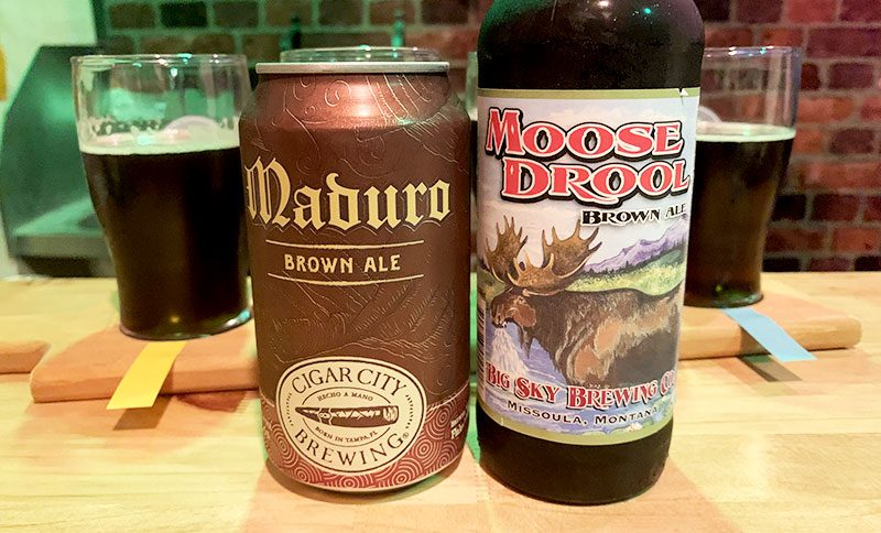 A fairly plain brown can of Maduro Brown Ale is shown alongside a bottle of Moose Drool Brown Ale, complete with Moose Illustration on the label.