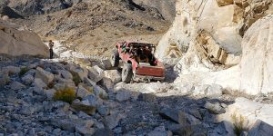 A red truck is shown traversing large boulders through a mountainous valley. Several people and a dog are seen in the bed of the truck.