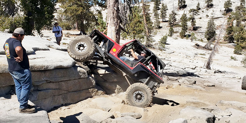 """A man in a four-wheel drive Jeep-style vehicle is seen with the front end of his vehicle atop a steep rock face of roughly 45 degrees, where the vehicle is in the process of """"crawling"""" up and over the barrier."""