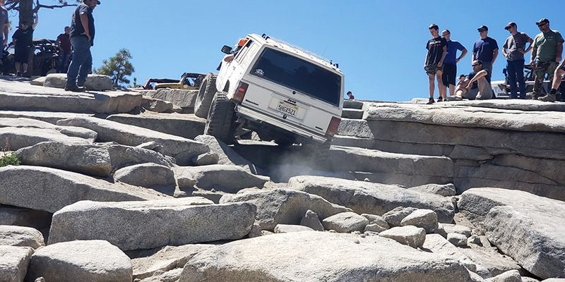 A group of onlookers watch a large white four-wheel drive vehicle tackle a long, extremely rocky portion of a large hill.