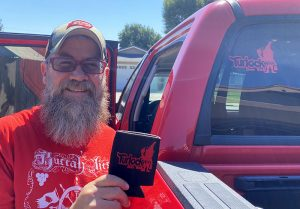 Heavily bearded Jay McElroy stands next to his pickup truck holding up the a beer koozie featuring the logo for the Turlock Area Beer Trolls group, with a matching logo sticker shown affixed to the back window of the truck's cab.