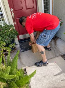 """Jay McElroy crouches outside the front door of an unsuspecting Turlock resident's home, trying to sneakily deliver a """"beer bomb"""" to the residence."""