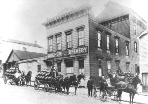An historical black and white photo of Anchor Brewing. Several horse-drawn cargo transports await their cargo.