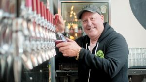 Julio Peix poses while pouring a beer from a very long row of other beers on tap.