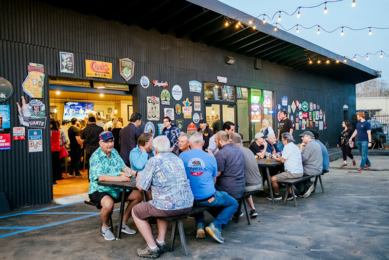 A large number of patrons is shown seating outside Lefty's during pre-pandemic times. A large assortment of new and vintage beer signs adorns the wall along the seating area.