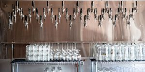 A wall loaded with three staggered rows of taps is featured behind the bar.
