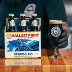 A six-pack of Ballast Point's Victory at Sea beer are shown alongside a gloved hand holding freshly-poured, stemmed-glass of the same.
