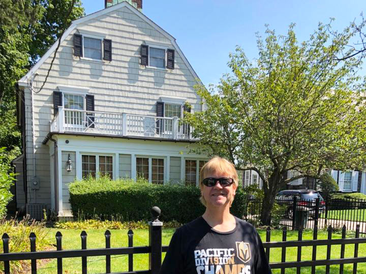 Charlie Snyder stands in front of the property associated with the Amityville horror film. Unlike in the 1979 movie, the house is painted a lighter color and the curved-on-one-side windows that looked like a set of eyes on the third floor are now rectangular. The home looks friendly, thought the metal fencing at the front of the home looks like it's there to keep the sightseers from wandering onto the property.