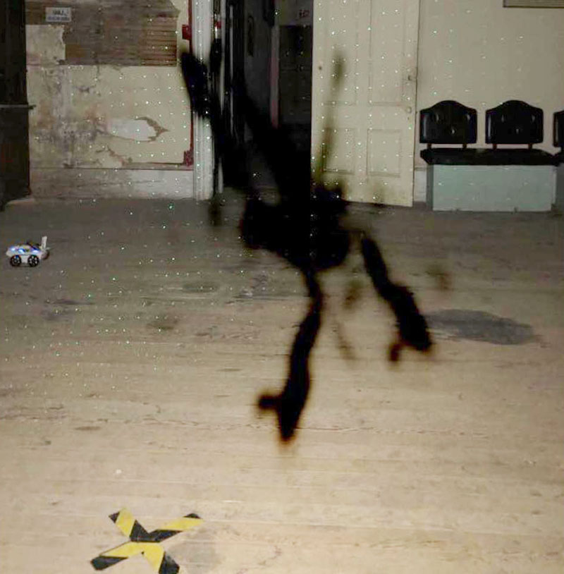 The interior of a large and empty ballroom floor shows a blackish, amorphous distortion captured on camera. There is also an amorphous shadowy distortion to the left of it. The blackish distortion is somewhat reminiscent of a Rorschach inkblot test..