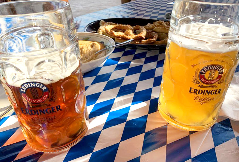 Two enormous Erdinger brand beer steins accompanied by homemade German pretzels and mustard, atop an Oktoberfest-themed tablecloth.