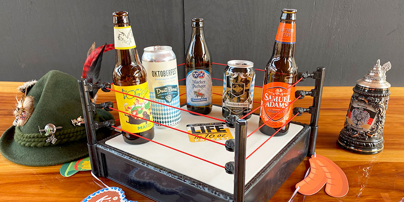 Five Oktoberfest-style bottles and cans beers are pictured in an actual, table-top, miniature boxing ring.