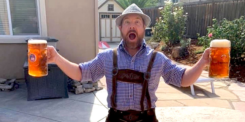Host Brandon McCarty poses in his lederhosen with a ginormous beer-filled stein in each hand.