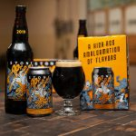 A freshly-poured, stemmed-glass of W00tstout stands alongside a can, bottle and packaging of the same.