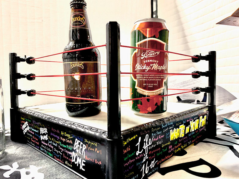 """A mini tabletop boxing ring is shown with two beers ready to do """"battle"""" on this month's Beer Dome."""