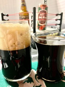 Two glasses of very, very dark beer, one of which has several inches of head atop of it while the other has nothing to show for.
