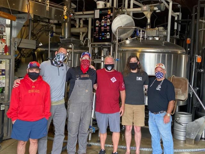 Posing in front of brewing tanks at Manor Hill Brewery are six of the eight men involved in brewing I Got Your Six.