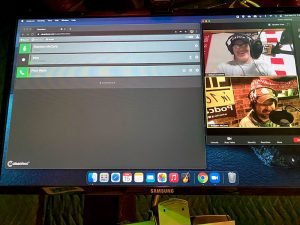 """Paul and Brandon are seen in small windows on a computer monitor with the Cleanfeed.net application open next to them, showing that their podcast is recording their """"call"""" for the show.."""