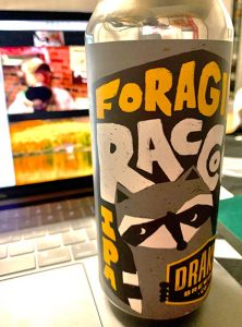 """Image of a tall can of beer with an artsy label featuring the trademark """"mask"""" of a racoon and ringed tail called, Foraging Raccoon IPA."""