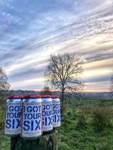 A six pack of a beer called, I Got Your Six, sits atop a fencepost with a lush, green countryside and sunset featured in the background.