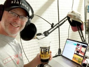 Paul Wade takes a selfie of himself in front of the mic in his recording studio with pint glass of beer in-hand, Brandon seen in a Zoom-like window on Paul's laptop.