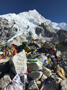 A large pile of rocks, some with writing on them, prayer flags, personal mementos left behind by visitors. A large snow-capped peak towers over the pile of mementos.