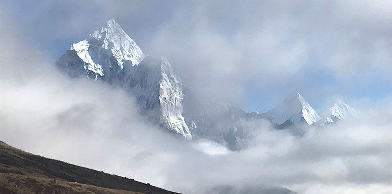Steep mountain peaks shown poking through clouds in the distance.