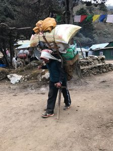 A man carrying an enormous load of goods stacked onto his back like an overpacked small pickup truck, leans on his walking stick as he treks through a village.