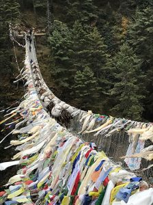 A very long suspension bridge loaded down with layer upon layer of prayer flags tied to the sides of the bridge with fully loaded yaks making their way across.