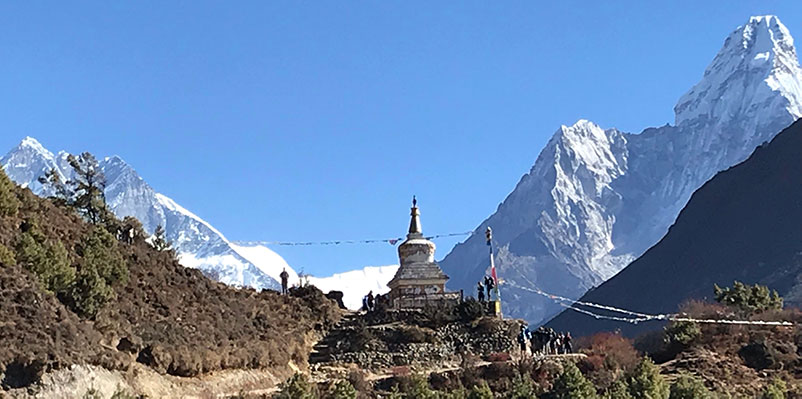 A prayer wheel marks the entrance to the next village on a trail, with enormous, snow-capped mountains in the backdrop.