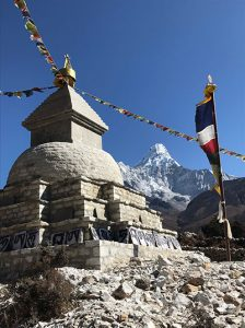 A prayer wheel structure features stings of prayer flags, with a high mountain peak seen in the background.