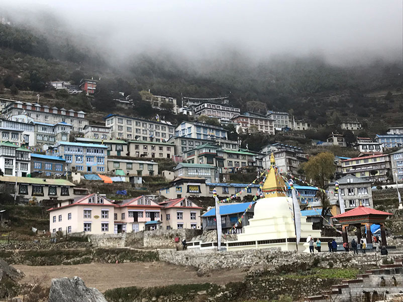 A sprawling, modern village covers the hillside of a cloud-covered mountain.