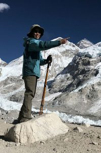Standing atop a rock and mountains behind her, Sherri Eng sports a big smile and points to something off camera.