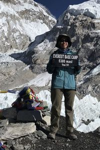 """Standing next to a """"marker"""" covered in prayer flags, Sherri Eng smiles and holds a sign that says, Everest Base Camp, 5380 masl, feui 91"""""""