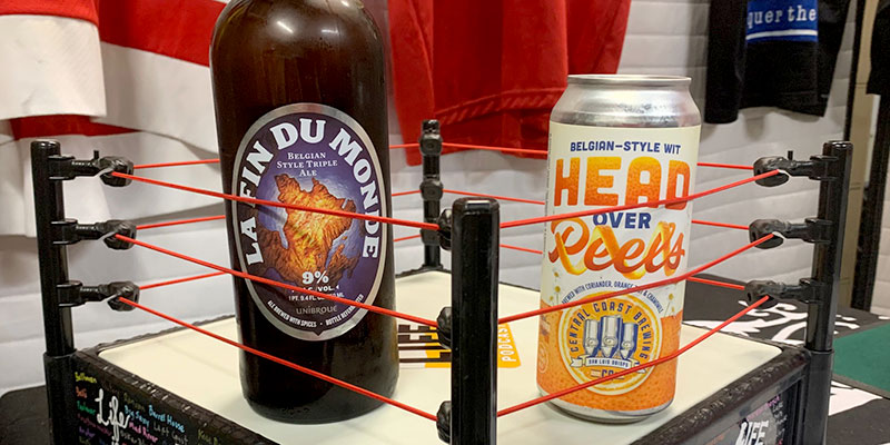 A brown bottle of Belgian style triple ale called La Fin du Monde is shown in a mini boxing ring next to a bright orange and yellowish can of a wheat beer called Head over Peels.