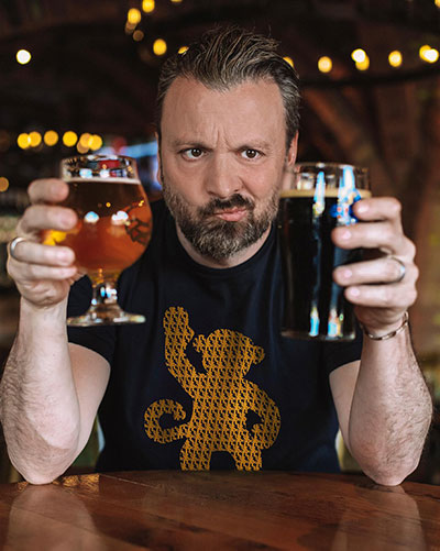 Zane Lamprey with an indecisive look on his face as he holds a light-colored, stemmed, half-pint of beer in one hand and a pint of dark beer in the other.