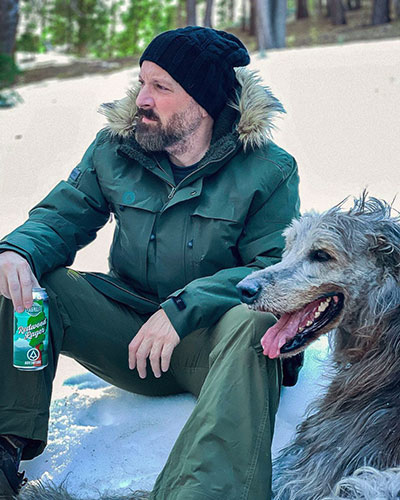 Zane Lamprey seated on the ground with his dog, can of Redwood Lager in hand, and sporting his Adv3nture brand jacket.
