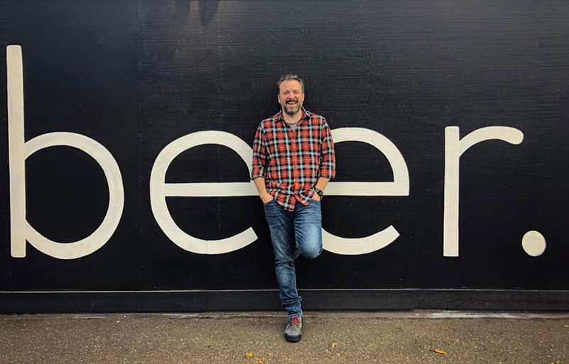 """Zane Lamprey leans against a wall with the word """"beer."""" in giant, white lettering behind him.."""