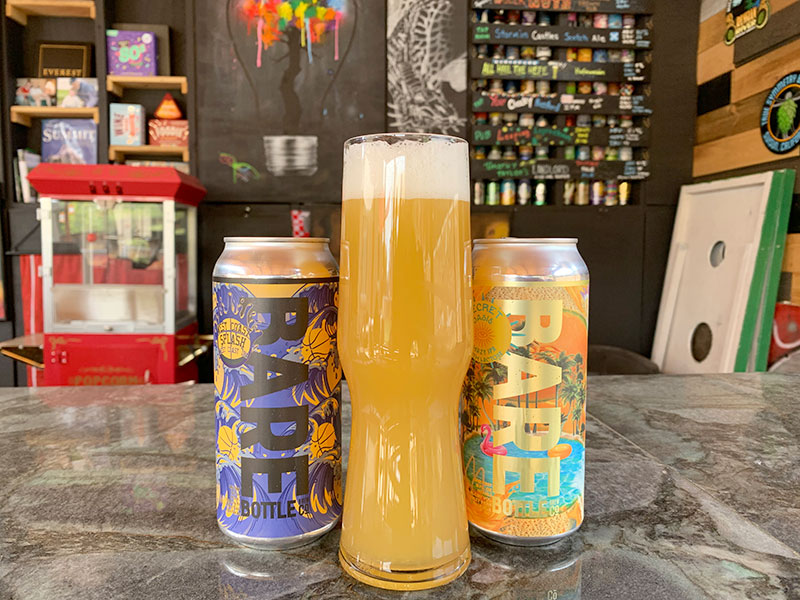 """Two cans of beer from Barebottle Brewing Company flank a tall, golden glass of beer in Paul's """"Pubvilion."""""""