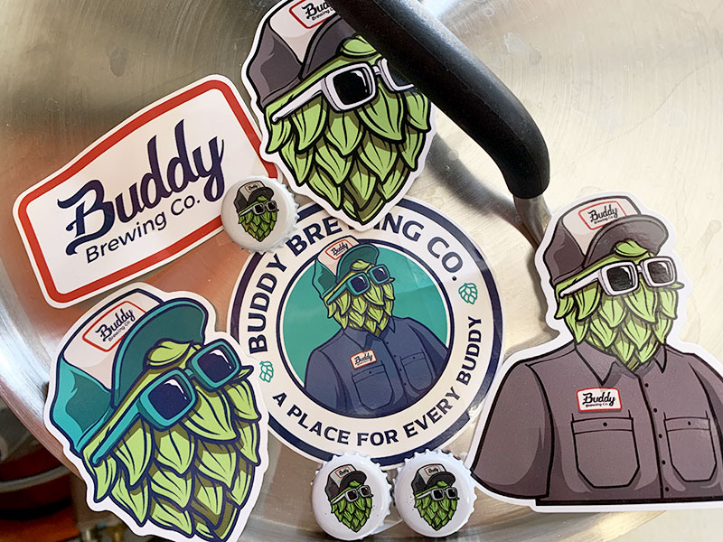 Stickers and bottle caps with a logo for Buddy Brewing Co. The logo features an illustration of a character with a hop-flower head wearing sunglasses and an old school gas station-type uniform.