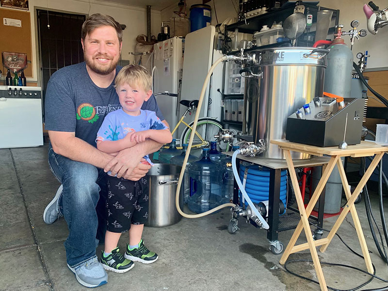 Brian Winckel and son pose in front of his brewing equipment, which includes a series of old refrigerators for his liquid gold.