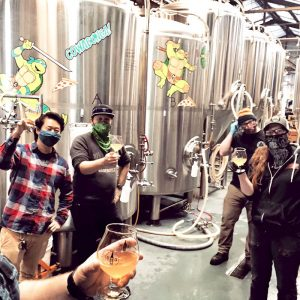 Lester, Magic, Kelsey lift their glasses for the camera on the production floor at Barebottle Brewing Company in San Francisco.