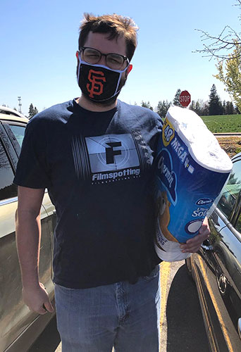 Thomas Todd poses wearing a mask and holding a pack of toilet paper.