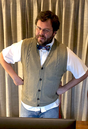 Button up sweater vest-wearing Thomas Todd glares at the camera, fists on hips, eyes squinting at the camera like the picture taker is in trouble.